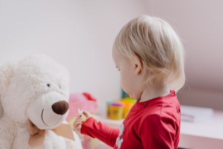 Little girl feeding her teddy