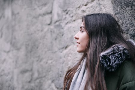 A girl leaning against a wall