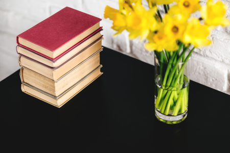 Spring daffodils and books on black table