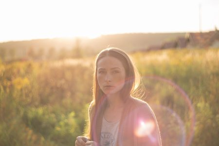 A girl in the meadow with sunflare