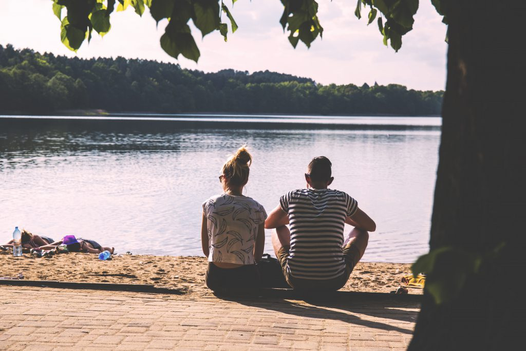 Couple sitting on the beach - free stock photo