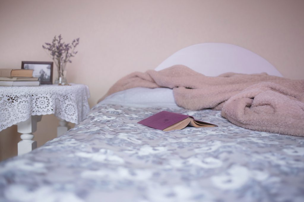 Open book on a bed - free stock photo