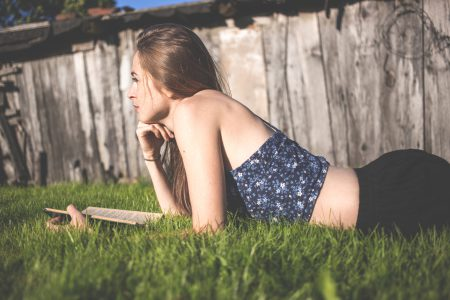 Pensive girl laying on grass - free stock photo