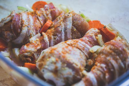 Raw chicken legs wrapped in bacon