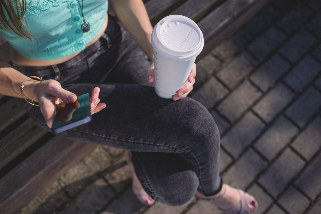 Girl holding phone and coffee - free stock photo