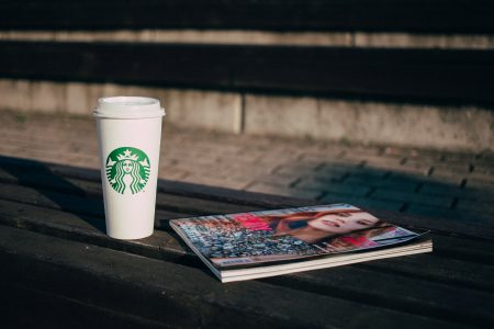 Coffee and a magazine on a bench