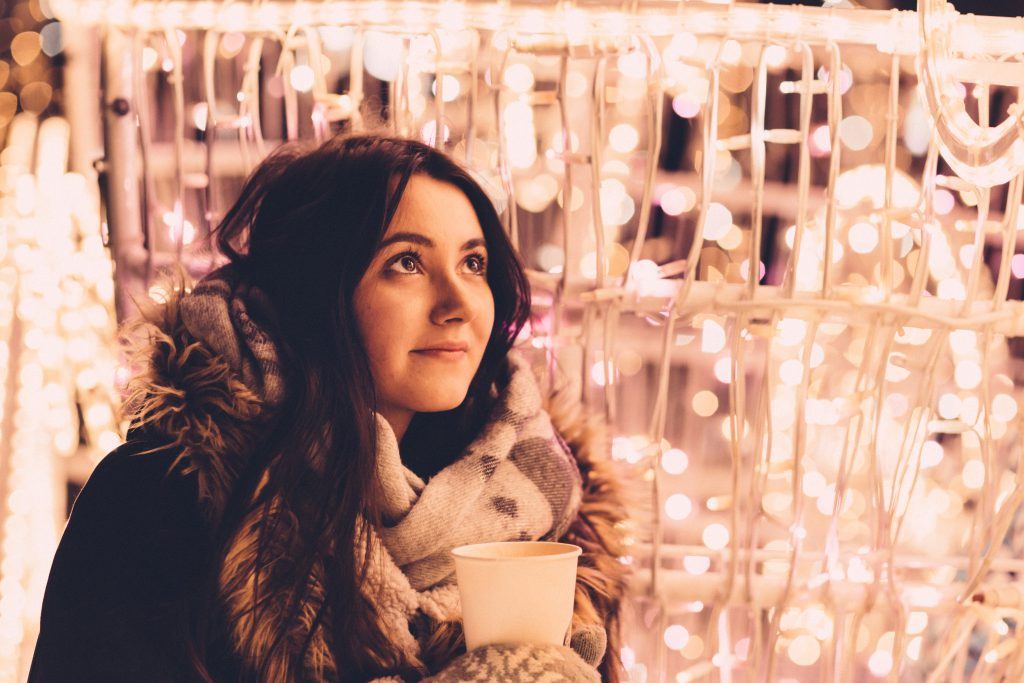 Christmas lights and a girl holding a coffee - free stock photo