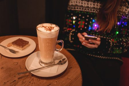 Girl in Christmas sweater sitting in a cafe