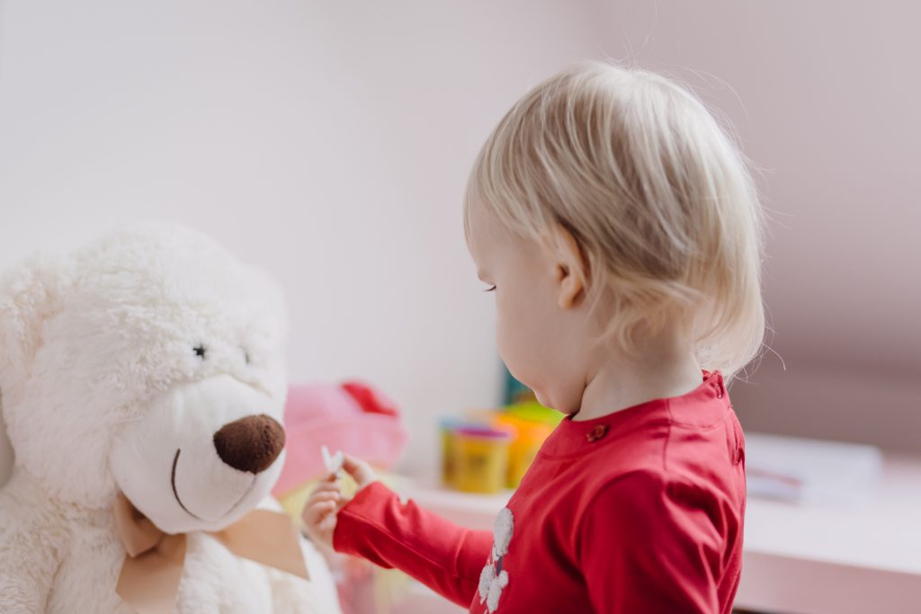 A little girl feeding her teddy - free stock photo