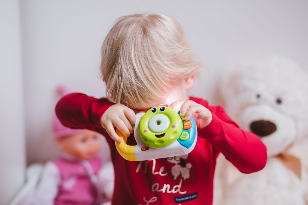 Little girl with a toy camera - free stock photo