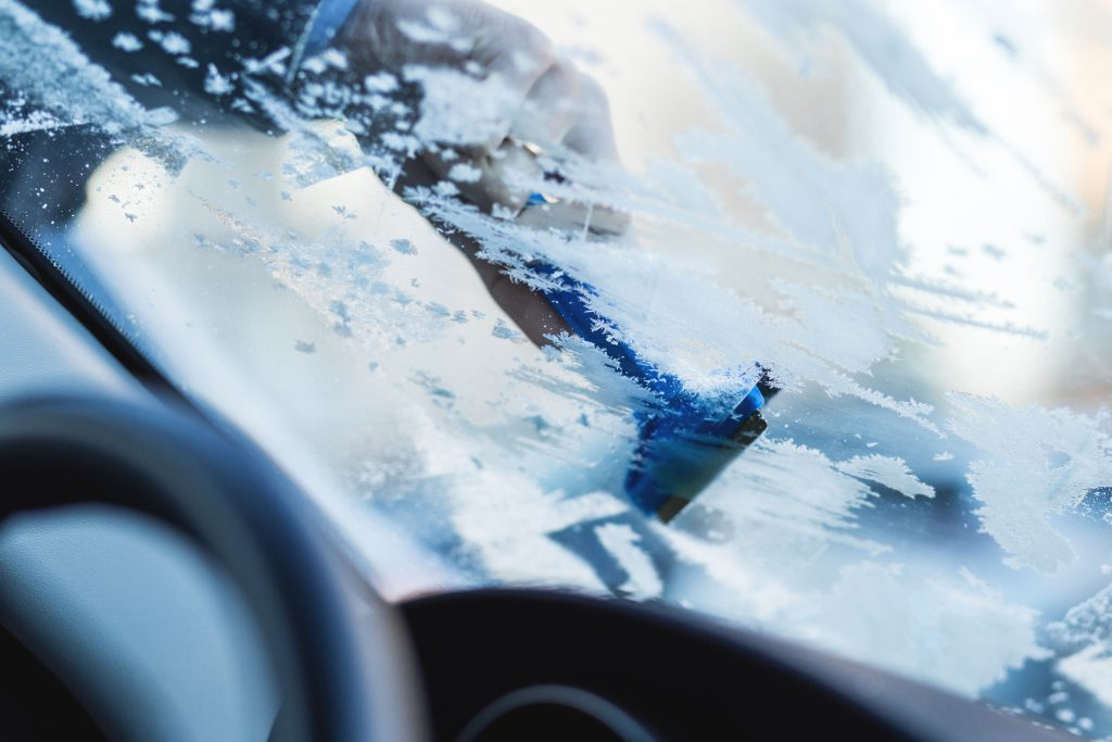 Removing frost from car windshield - free stock photo