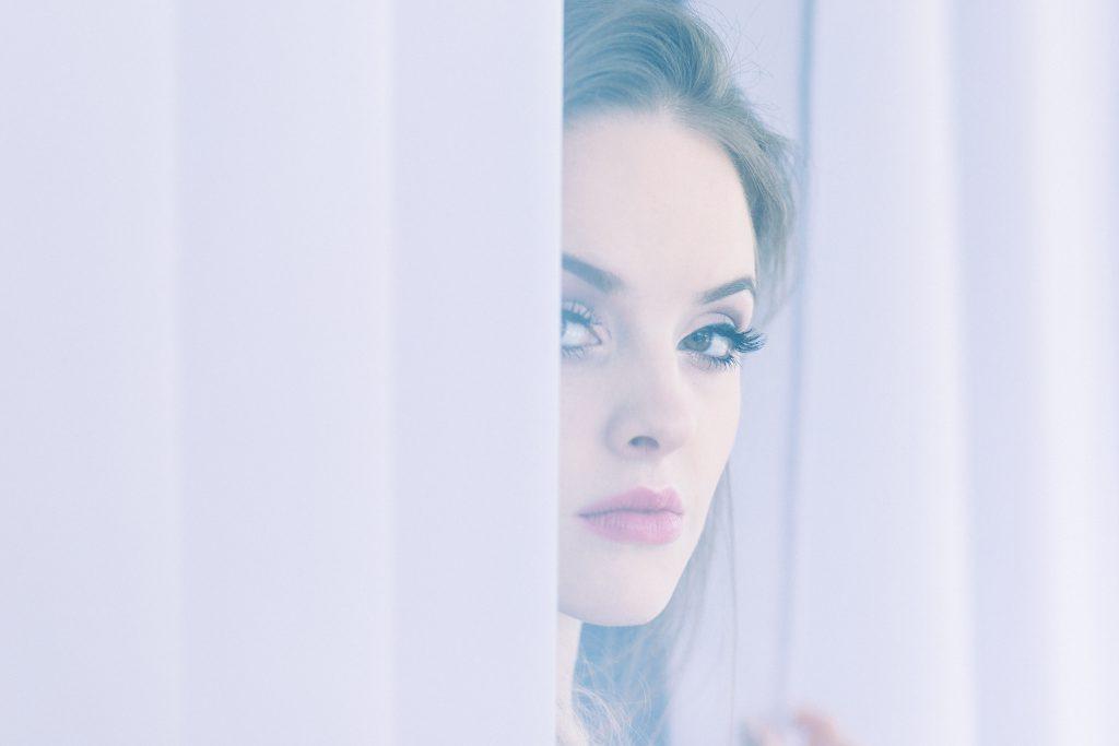 A woman peering through curtains - free stock photo