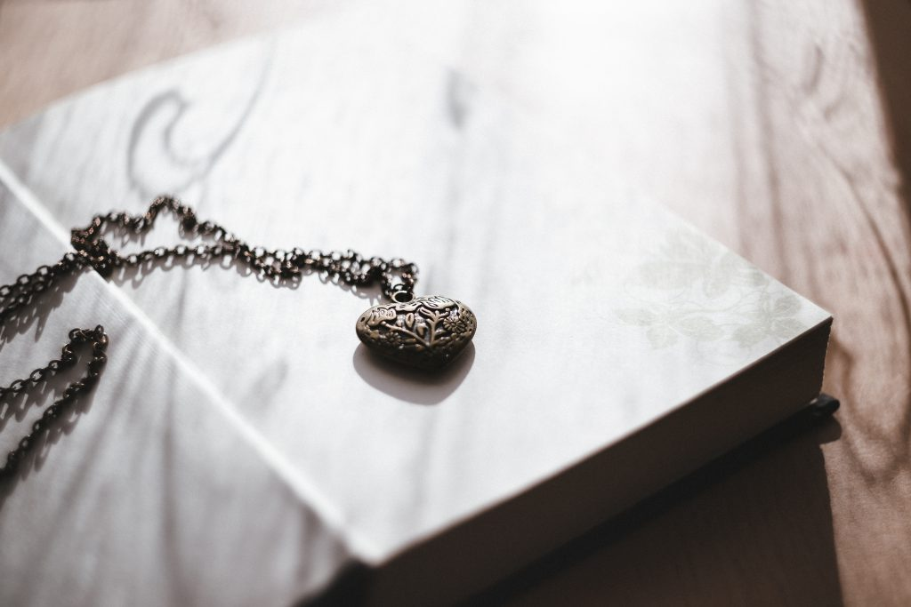 Heart necklace on an open book - free stock photo