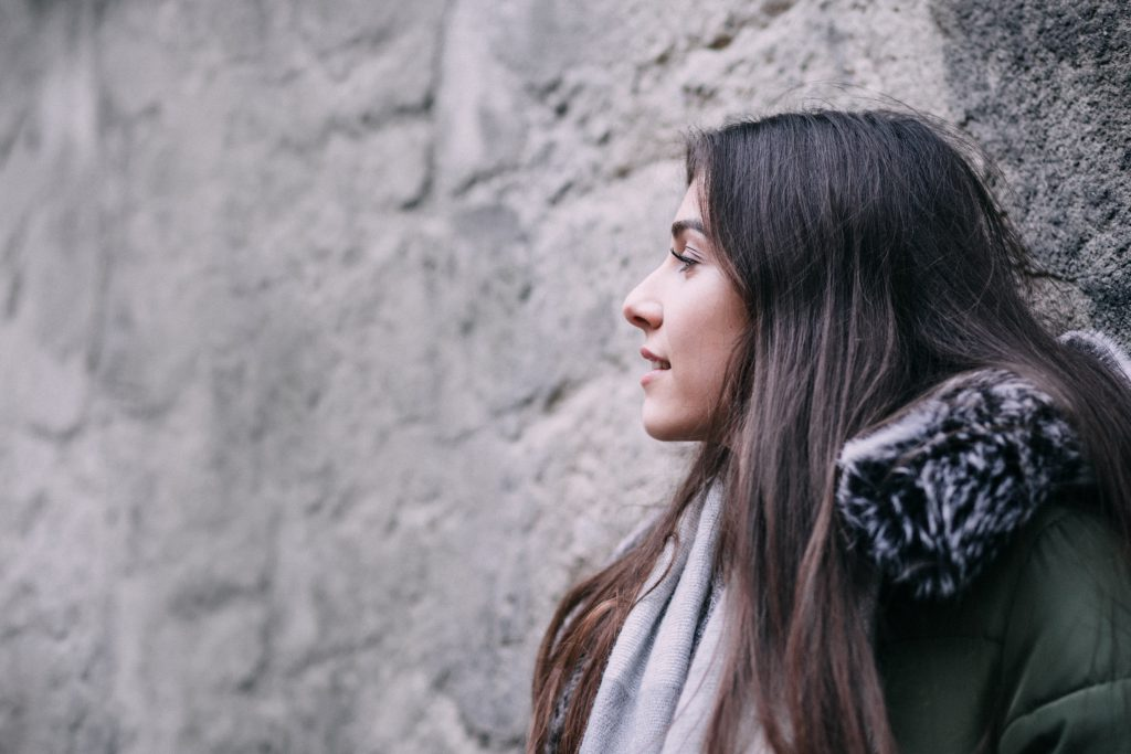 A girl leaning against a wall - free stock photo