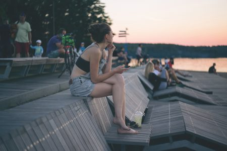 A girl with the phone sitting at the lake - free stock photo