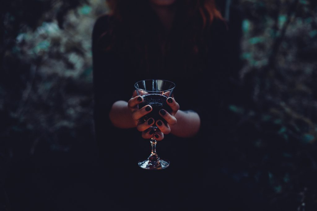 A witch holding a glass of wine - free stock photo