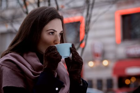 A woman drinking coffee outdoors 2