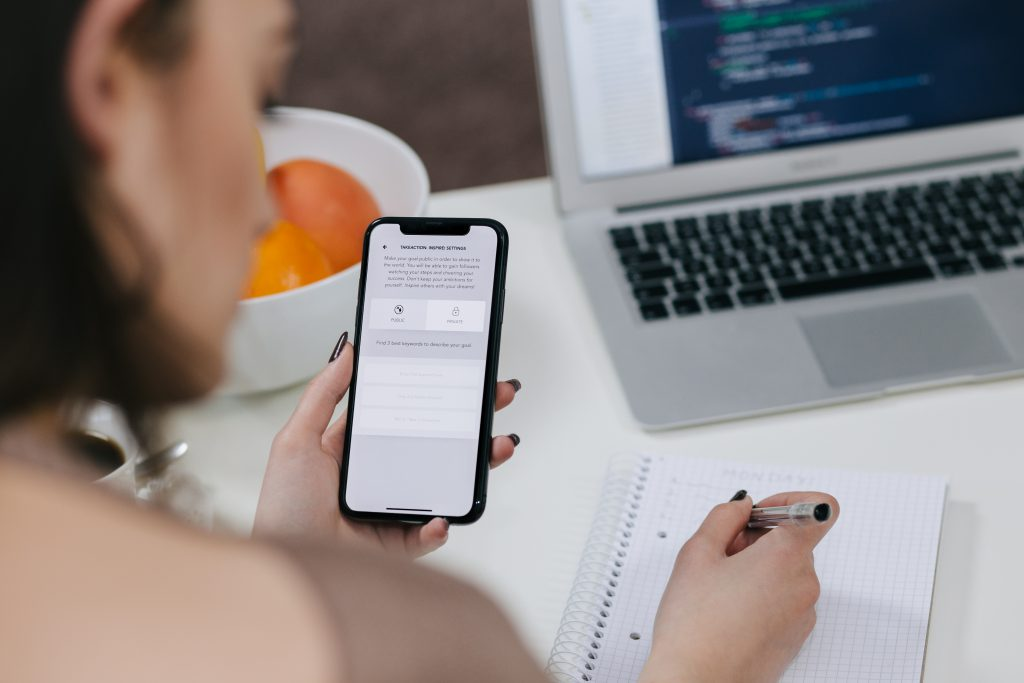Female holding an iPhone X and taking notes - free stock photo