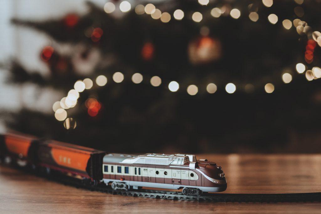 Toy train going around the Christmas tree - free stock photo