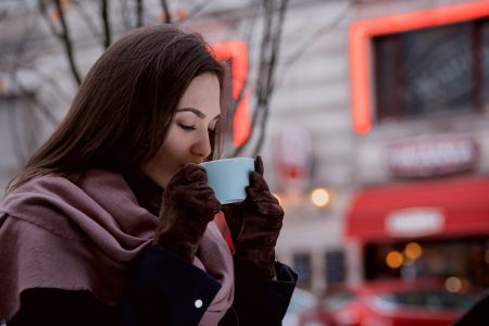 A woman drinking coffee outdoors - free stock photo
