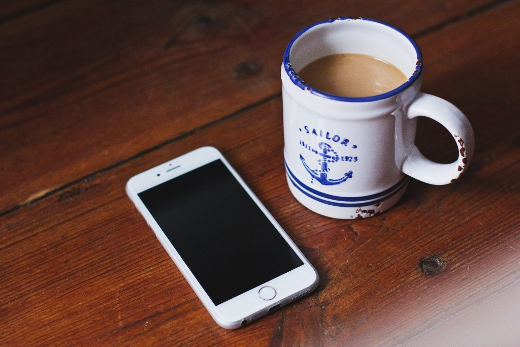Oldschool mug of latte and an iPhone - free stock photo