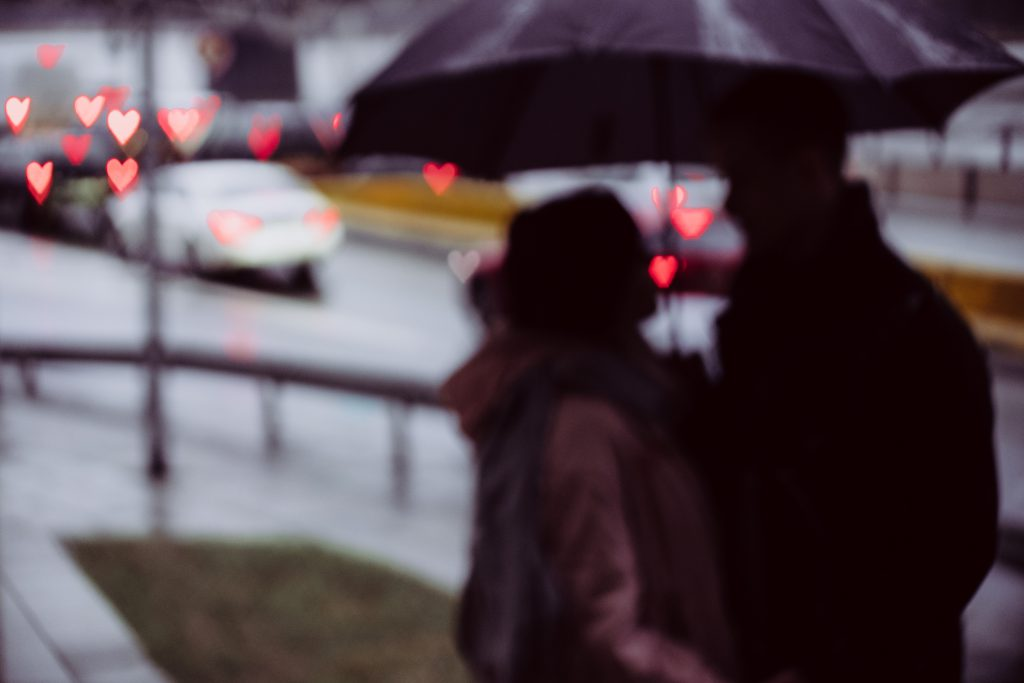 Couple silhouettes and traffic lights heart shaped bokeh - free stock photo