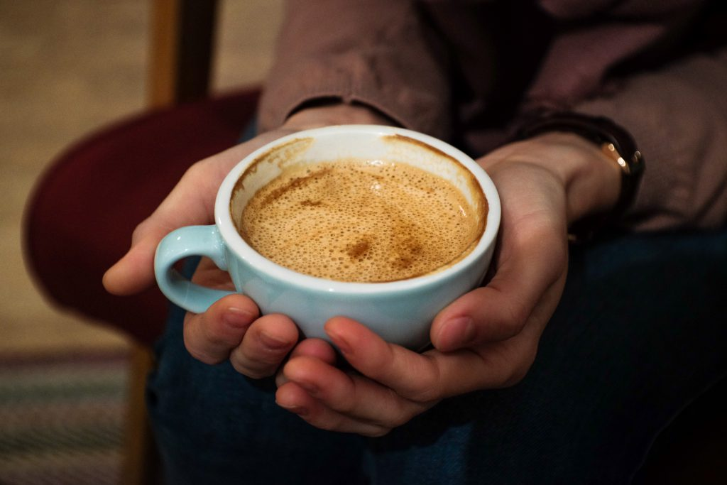 Cup of flat white in female hands - free stock photo