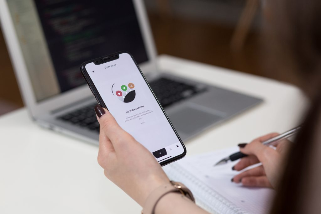 A female holding an iPhone X and taking notes 3 - free stock photo