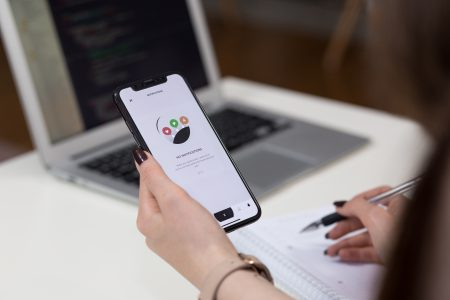 Female holding an iPhone X and taking notes 3