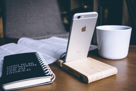 iPhone in a wooden phone holder - free stock photo