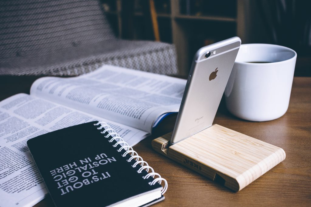iPhone in a wooden phone holder 4 - free stock photo