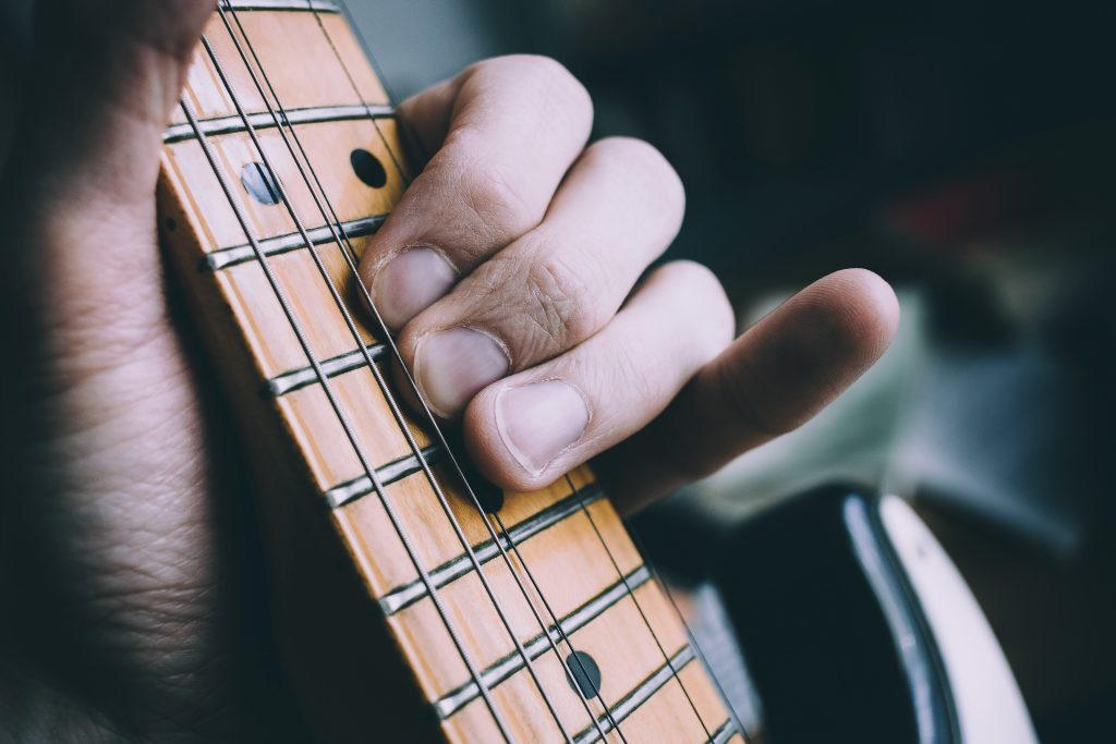 Guitarist hand playing guitar - free stock photo