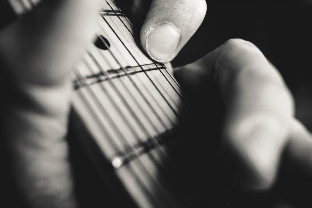 Guitarist hand playing guitar closeup - free stock photo