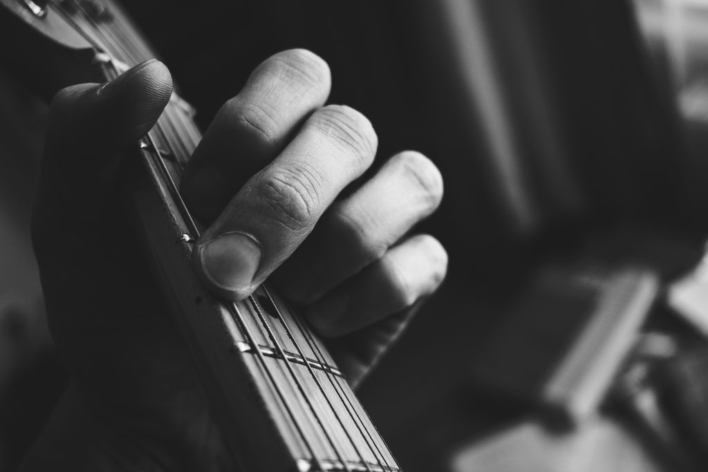 Guitarist hand playing guitar in black and white - free stock photo