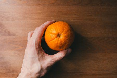 Orange in a male hand - free stock photo