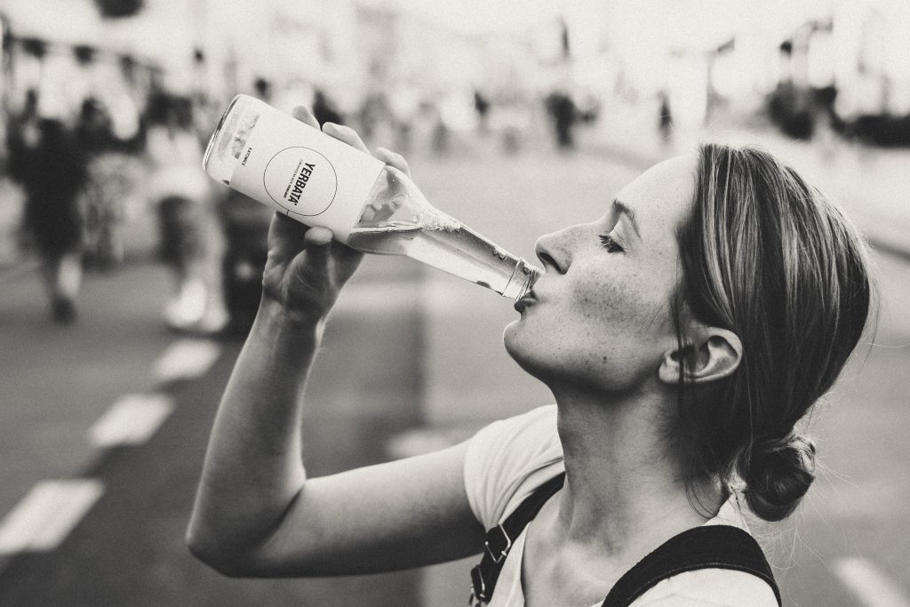 Female drinking soda from a glass bottle - free stock photo