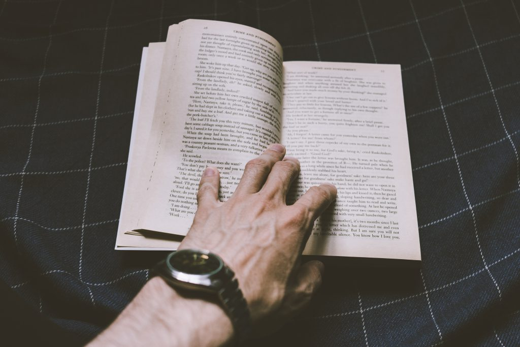 Male hand holding an open book - free stock photo