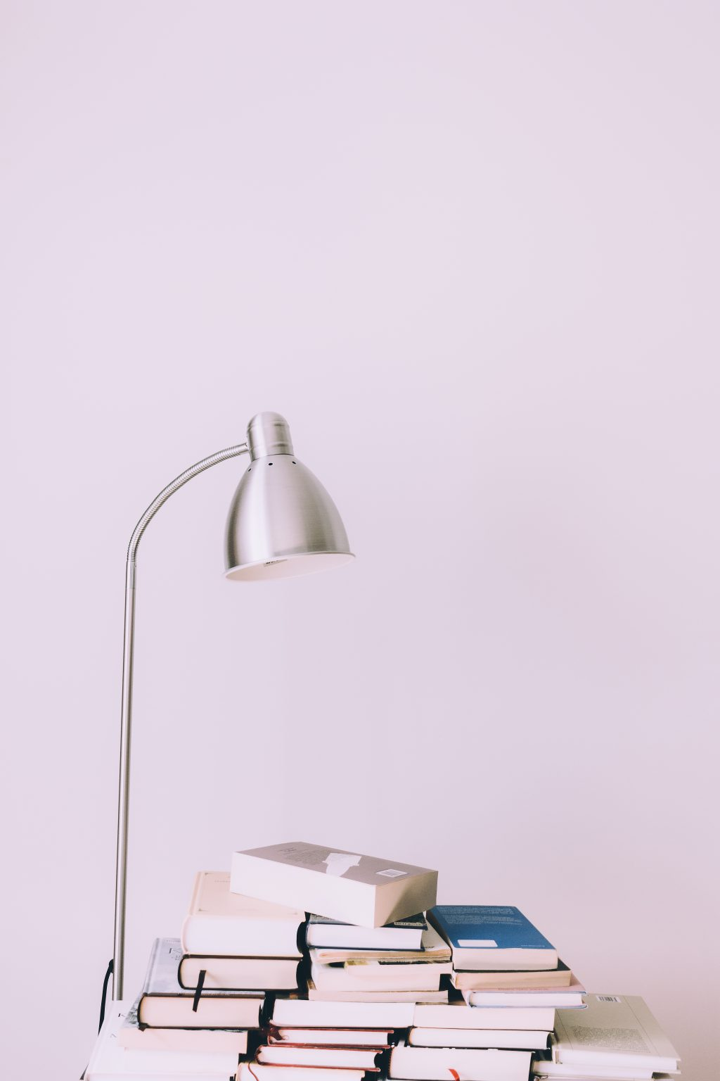 Metal desk lamp and books pile - free stock photo
