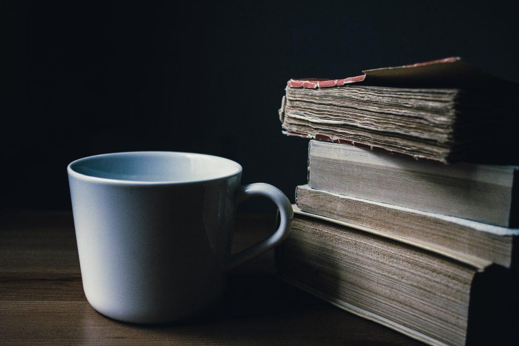 Tea mug and a pile of books - free stock photo