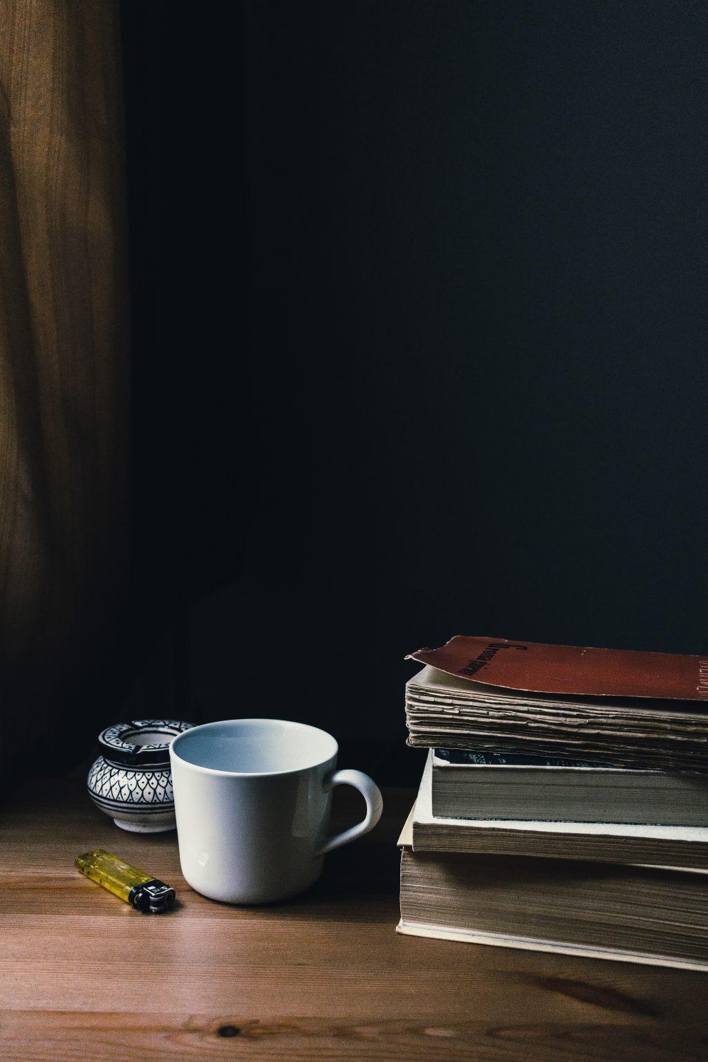 Tea mug, a lighter and a pile of books - free stock photo