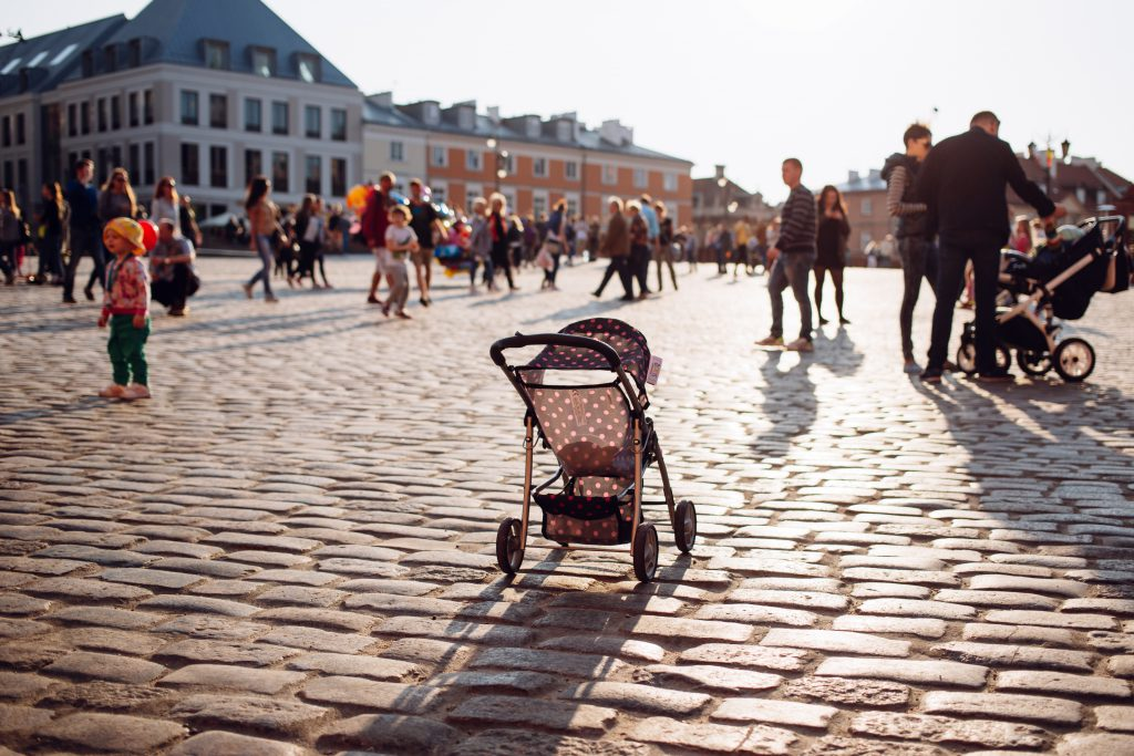 An empty stroller in a crowded Old Town square - free stock photo