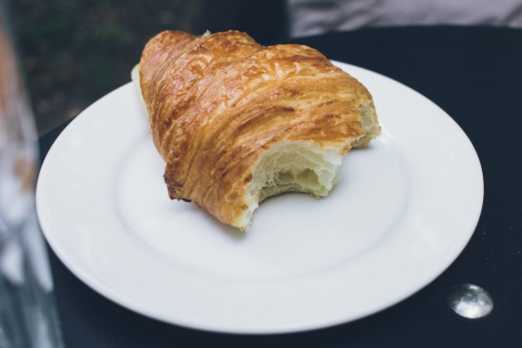 Bitten butter croissant on a plate - free stock photo