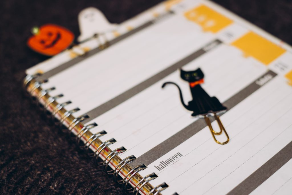 Black cat, a pumpkin and a ghost paperclips in a calendar - free stock photo