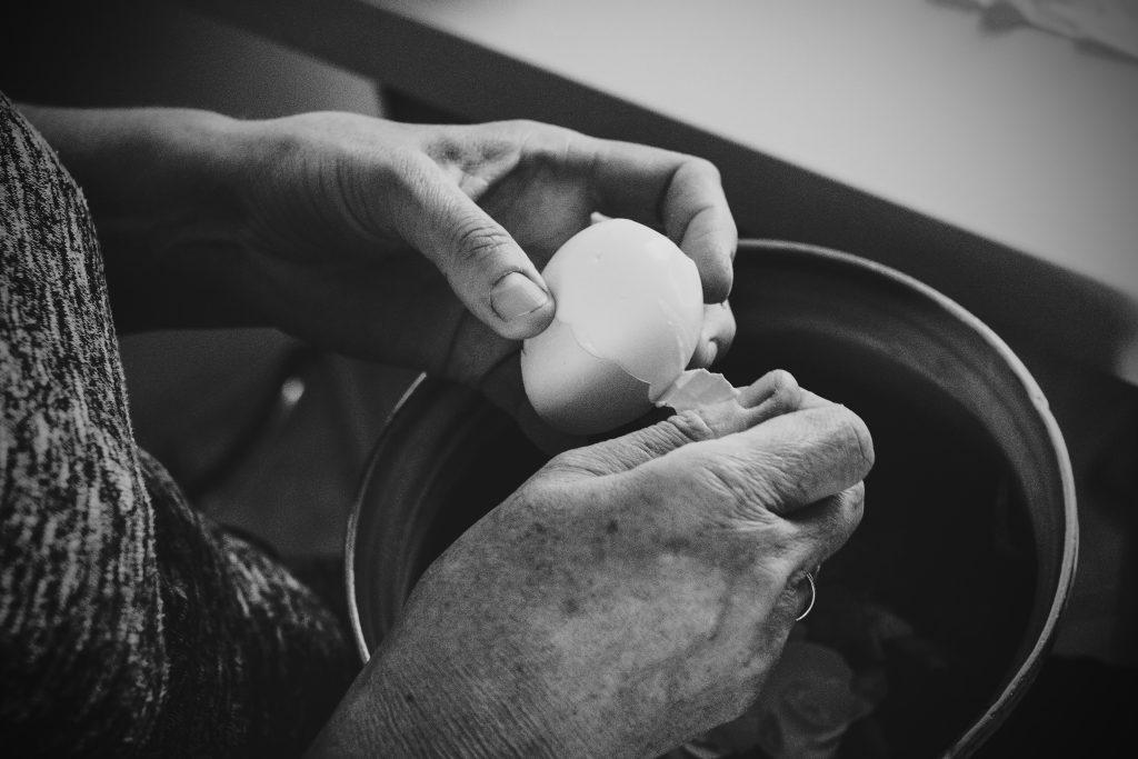 Old woman peeling an egg - free stock photo