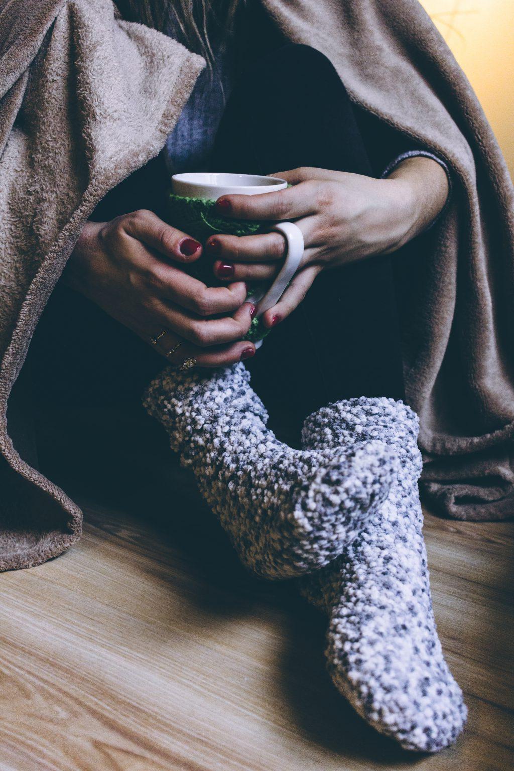 A female in warm socks holding a mug - free stock photo