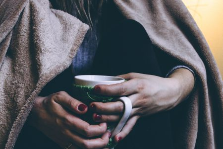 A female in warm socks holding a mug - free stock photo