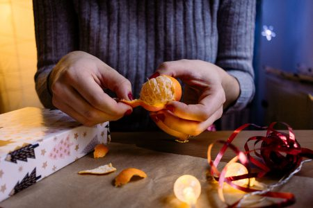 A female peeling a mandarin in a festive setting - free stock photo