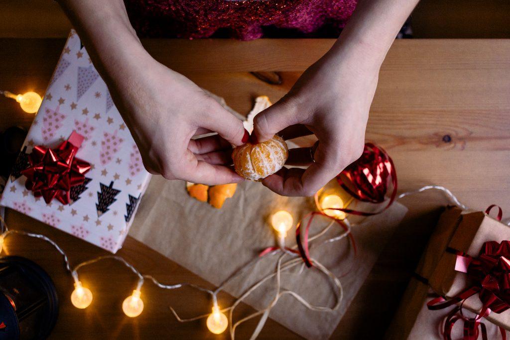 A female peeling a mandarin in a festive setting 2 - free stock photo