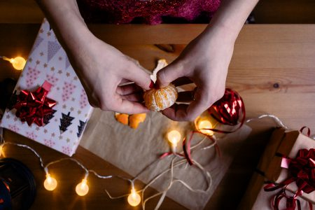 A female peeling a mandarin in a festive setting 2 - free stock photo