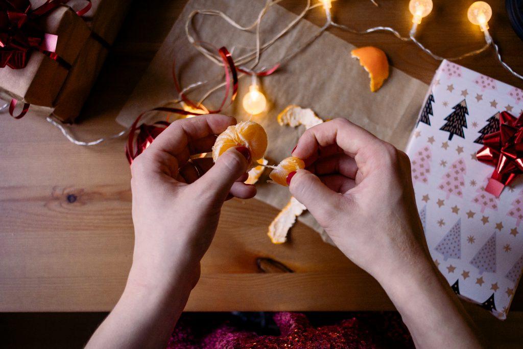 A female peeling a mandarin in a festive setting 3 - free stock photo